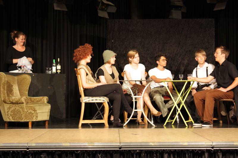 David Shayne (dritter von rechts) im Kreise anderer Literaten, beobachtet von Lehrerin Judith Weyermann in der Rolle der Barfrau. Lisa Herzog (dritte von links) spielt hier eine Autorin.