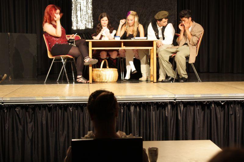 Gangsterbraut Olive (am Tisch in der Mitte) blamiert sich schon bei der ersten Probe zu Shaynes neuem Theaterstück – unter den Augen von Shaynes Verlegerin, gespielt von Melanie Katterbach (Vordergrund).